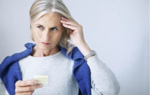 Elderly woman holding a piece of paper having issues recalling something due to poor memory