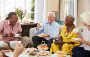 A group of senior friends enjoying afternoon tea and some food together