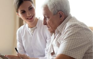 A caregiver assisting a senior man who is having difficulty writing due to Alzheimer's