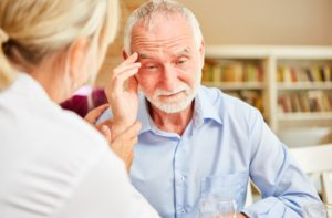 A senior man with signs of Alzheimer's comforted by a female memory caregiver